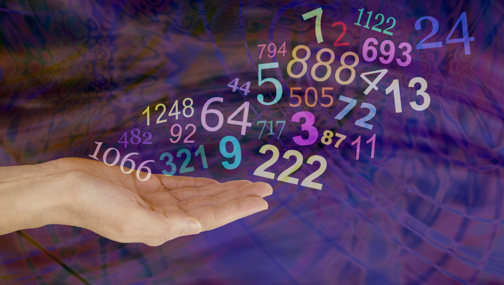 What do your Numbers mean - female hand palm up with a group   of random multicolored transparent numbers floating up and away on a dark multicolored background with copy space